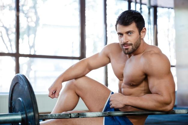 Portret van een knappe mannelijke bodybuilder die in de fitnesszaal rust