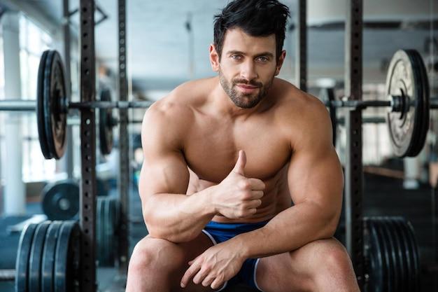 Portret van een knappe mannelijke bodybuilder die op de bank in de fitnessruimte zit en duim omhoog laat zien