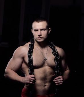 Portret van een knappe mannelijke bodybuilder met een ketting om zijn nek. foto met kopie ruimte