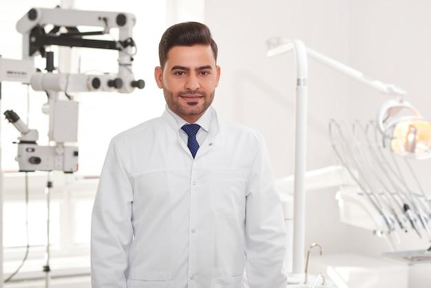 Portret van een knappe mannelijke tandarts die zich voordeed op zijn kantoor
