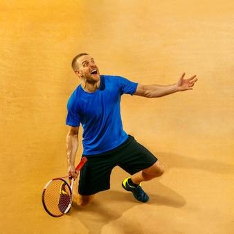 Portret van een knappe mannelijke tennisser die zijn succes op een hofmuur viert. menselijke emoties, winnaar, sport, overwinningsconcept