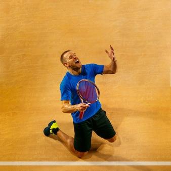 Portret van een knappe mannelijke tennisser die zijn succes op een hofmuur viert