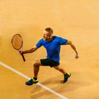 Portret van een knappe mannelijke tennisser die zijn succes op een hofmuur viert Gratis Foto
