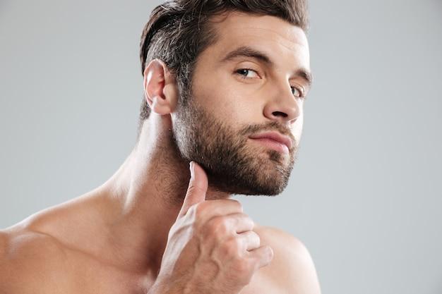 Portret van een knappe naakte bebaarde man onderzoekt zijn gezicht