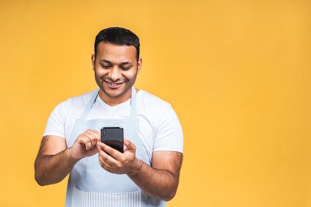 Portret van een knappe, opgewekte, vrolijke, indiase afro-amerikaanse kok die nonchalant verzendt en berichten ontvangt die over een gele achtergrond worden geïsoleerd. telefoon gebruiken, recept zoeken.