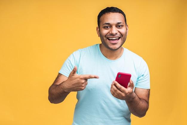 Portret van een knappe opgewonden vrolijke indiase afro-amerikaanse man die casual berichten naar zijn geliefde verzendt en ontvangt, geïsoleerd op gele achtergrond. telefoon gebruiken.