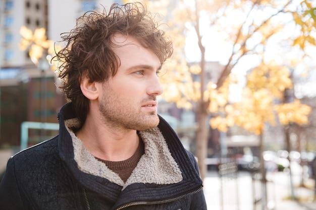 Portret van een knappe peinzende, aantrekkelijke, gekrulde man in een zwarte jas die door de stad loopt