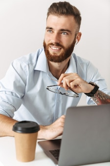 Portret van een knappe positieve vrolijke optimistische jonge zakenman geïsoleerd poseren op witte muur met behulp van laptopcomputer zitten aan de tafel luisteren muziek met oortelefoons.