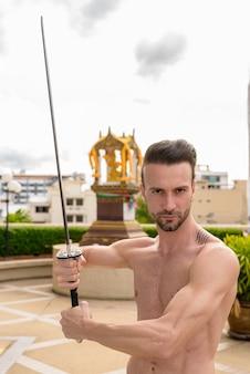 Portret van een knappe shirtloze man die buiten een zwaard vasthoudt