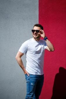 Portret van een knappe stijlvolle man, een man gekleed in een wit leeg t-shirt dat op een grijze en rode muurachtergrond staat. stedelijke kledingstijl, modern modieus beeld. herenmode