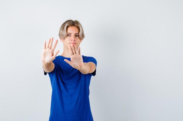 Portret van een knappe tienerjongen die een stopgebaar in een blauw t-shirt laat zien en er bang vooraanzicht uitziet