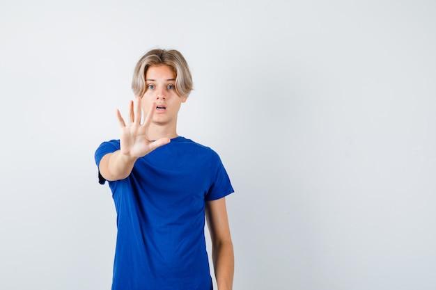 Portret van een knappe tienerjongen die een stopgebaar in een blauw t-shirt toont en een bang vooraanzicht ziet