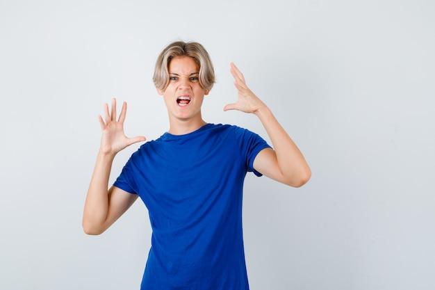 Portret van een knappe tienerjongen die klauwen laat zien die een kat imiteren terwijl hij in een blauw t-shirt schreeuwt en er geïrriteerd vooraanzicht uitziet