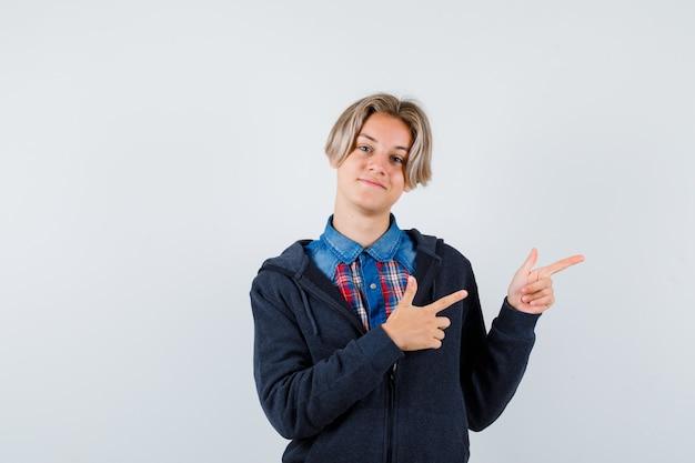 Portret van een knappe tienerjongen die recht in shirt, hoodie wijst en er vrolijk vooraanzicht uitziet