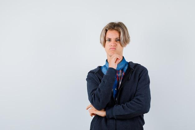 Portret van een knappe tienerjongen die zijn kin in zijn shirt, hoodie steekt en er ontevreden vooraanzicht uitziet
