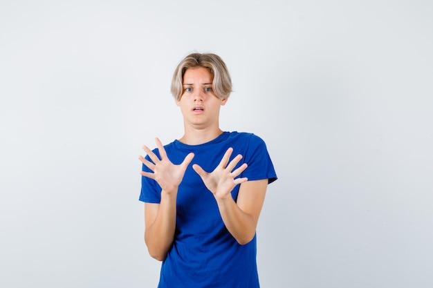 Portret van een knappe tienerjongen met een overgavegebaar in een blauw t-shirt en een angstig vooraanzicht