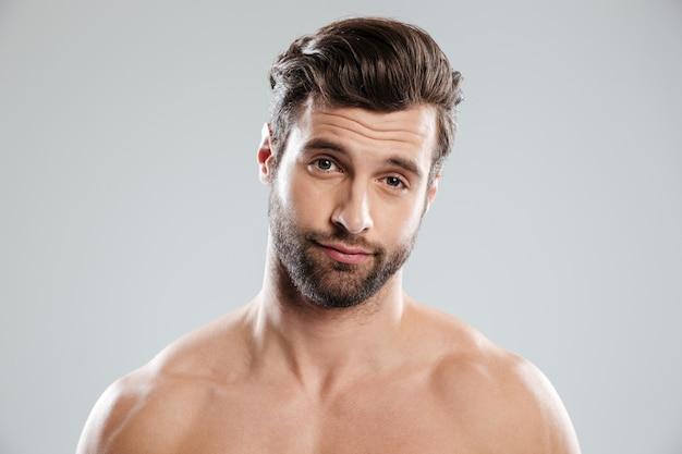Portret van een knappe twijfelachtige man met blote schouders