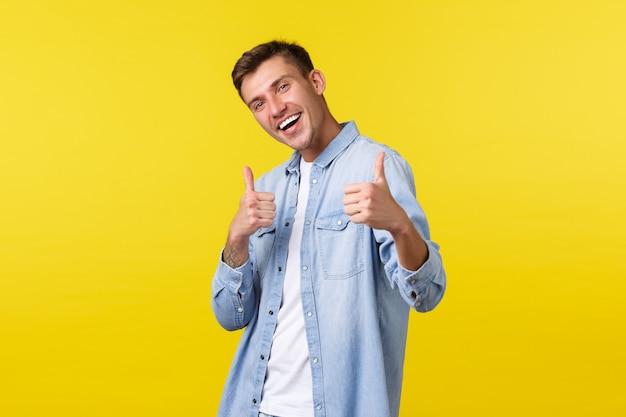Portret van een knappe, uitgaande blonde man die zijn duim omhoog laat zien ter goedkeuring, moedigt een bezoek aan de winkel aan. mannelijke student die mensen uitnodigt voor zomerevenementen of cursussen met speciale korting, gele achtergrond.