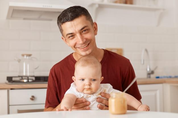 Portret van een knappe vader die een bordeauxrood t-shirt draagt met een charmante dochter, haar peutermeisje voedt, glimlachend naar de camera kijkt en geluk uitdrukt.