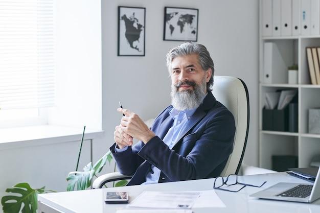 Portret van een knappe, volwassen, bebaarde man in een pak met een pen aan de kantoortafel