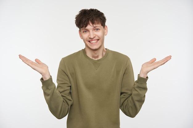 Portret van een knappe, volwassen man met donkerbruin haar, piercings en borstelharen. het dragen van een kaki kleur trui. spreid zijn armen en toont onwetendheid. geïsoleerd over witte muur