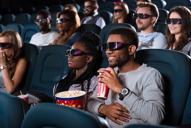 Portret van een knappe vrolijke afrikaanse man die lacht tijdens het kijken naar een 3d-film met zijn vriendin in de bioscoop