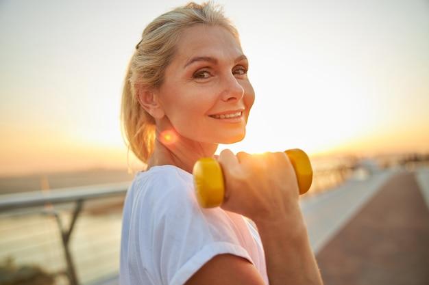 Portret van een knappe, vrolijke atletische vrouw van middelbare leeftijd met een halter die voor de camera poseert