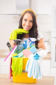 Portret van een knappe vrouw met hoofd rustend op een rubberen handschoen, glimlachend en leunend tegen een emmer vol schoonmaakspullen.
