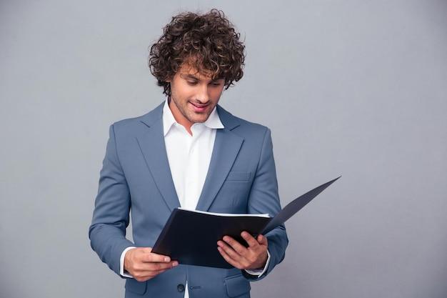 Portret van een knappe zakenman die documenten in omslag over grijze muur leest