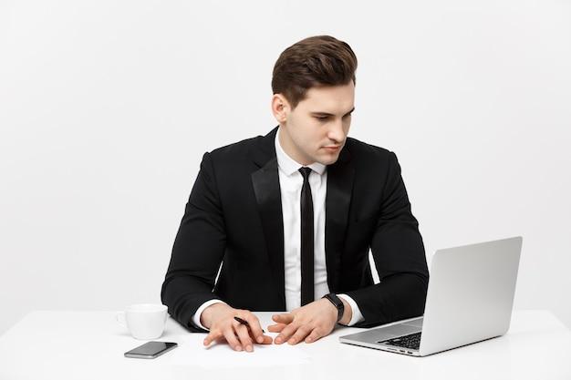 Portret van een knappe zakenman die een smartphone vasthoudt terwijl hij op een computer aan zijn bureau werkt.