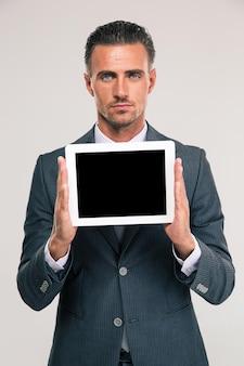 Portret van een knappe zakenman die het lege geïsoleerde scherm van de tabletcomputer toont