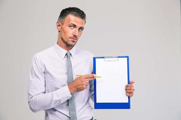 Portret van een knappe zakenman die leeg klembord geïsoleerd toont