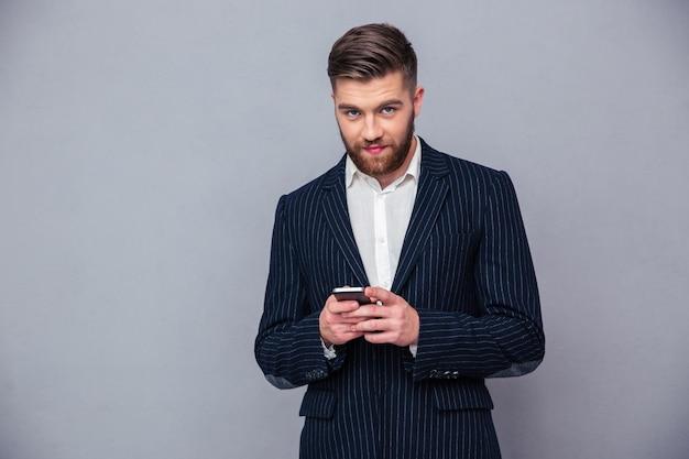 Portret van een knappe zakenman die smartphone over grijze muur gebruikt en camera bekijkt