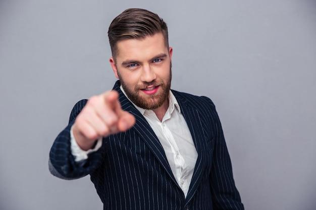 Portret van een knappe zakenman die vinger richt op camera over grijze muur