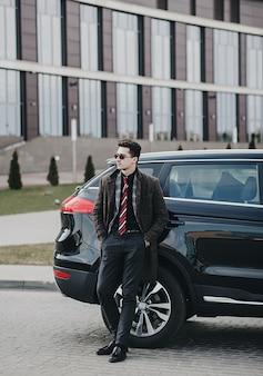 Portret van een knappe zakenman die zich dichtbij de auto buiten dichtbij modern gebouw bevindt