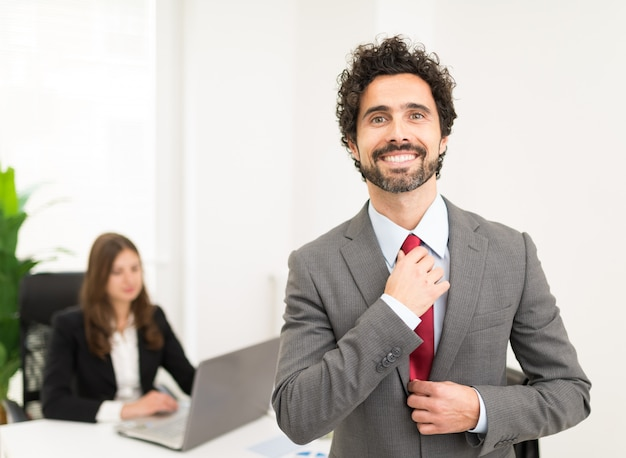 Portret van een knappe zakenman die zijn band aanpast
