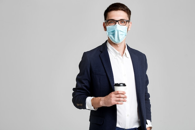 Portret van een knappe zakenman in brillen en gezichtsmasker met een kopje koffie.