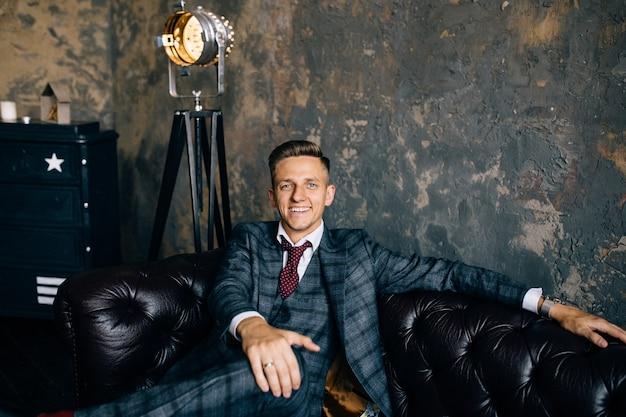 Portret van een knappe zakenman in pak op een luxe vintage lederen bank