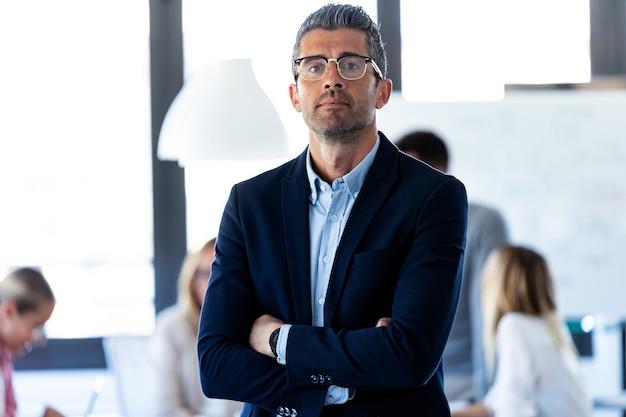 Portret van een knappe zakenman kijkt naar de camera terwijl zijn collega's aan een coworking-plek werken.