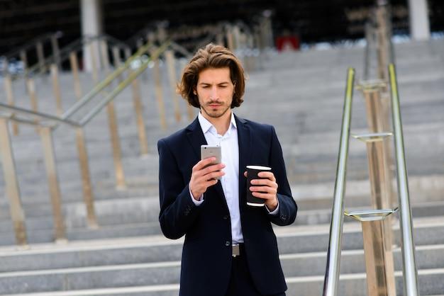 Portret van een knappe zakenman met telefoon, koffiekopje in de straten van de stad