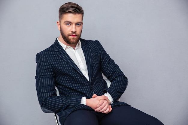 Portret van een knappe zakenman zittend op de bureaustoel over grijze muur