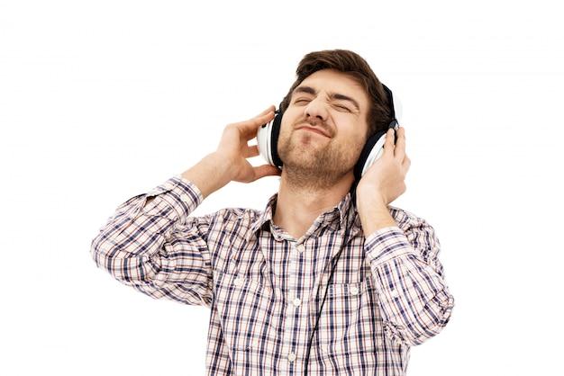 Portret van een knappe zelfverzekerde man, zingen in hoofdtelefoons