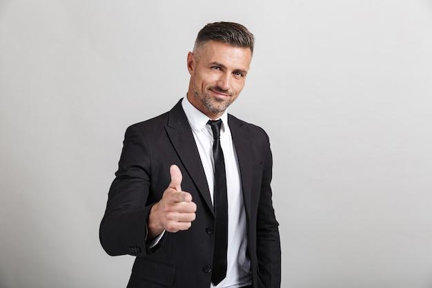 Portret van een knappe zelfverzekerde zakenman die een pak draagt dat geïsoleerd staat en zijn duimen opsteekt