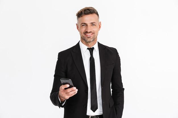Portret van een knappe zelfverzekerde zakenman die een pak draagt dat geïsoleerd staat, met behulp van mobiele telefoon
