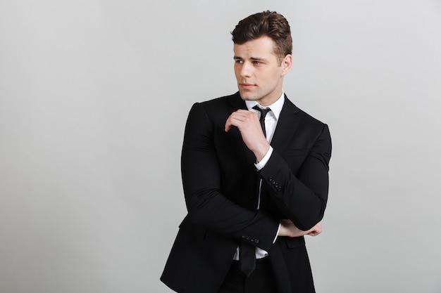 Portret van een knappe zelfverzekerde zakenman die een pak draagt dat geïsoleerd staat, wegkijkt, poseert