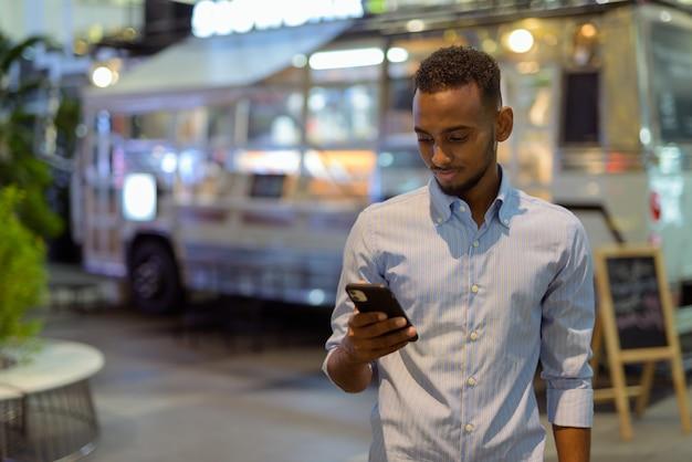 Portret van een knappe zwarte afrikaanse zakenman buiten in de stad 's nachts met behulp van een horizontale opname van een mobiele telefoon