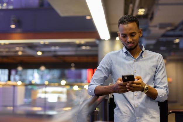 Portret van een knappe zwarte afrikaanse zakenman in een winkelcentrum die sms't met een horizontaal schot van een mobiele telefoon