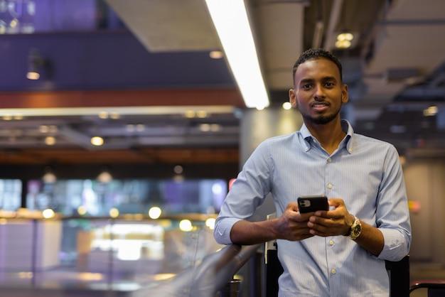 Portret van een knappe zwarte afrikaanse zakenman in een winkelcentrum met behulp van een horizontaal schot van de mobiele telefoon