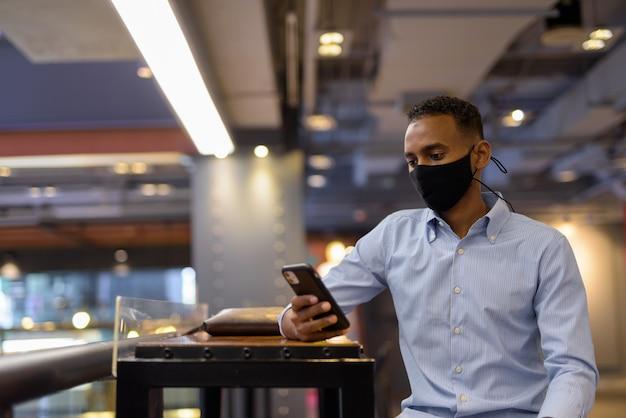 Portret van een knappe zwarte afrikaanse zakenman in een winkelcentrum met een gezichtsmasker en een horizontale opname van een mobiele telefoon