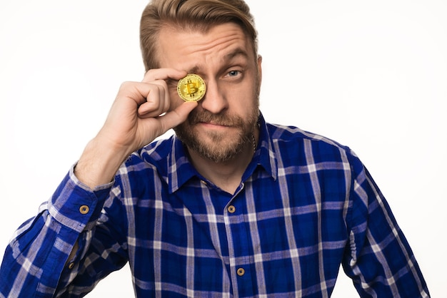 Portret van een knipogende man houdt een muntstuk bitcoin voor zijn oog geïsoleerd op wit